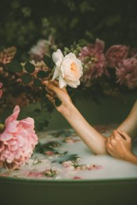 Self-Care Habits - Woman in a milk bath with flowers