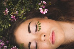Self-Care Habits - Woman sleeping in nature surrounded by flowers with leaves under her eyes