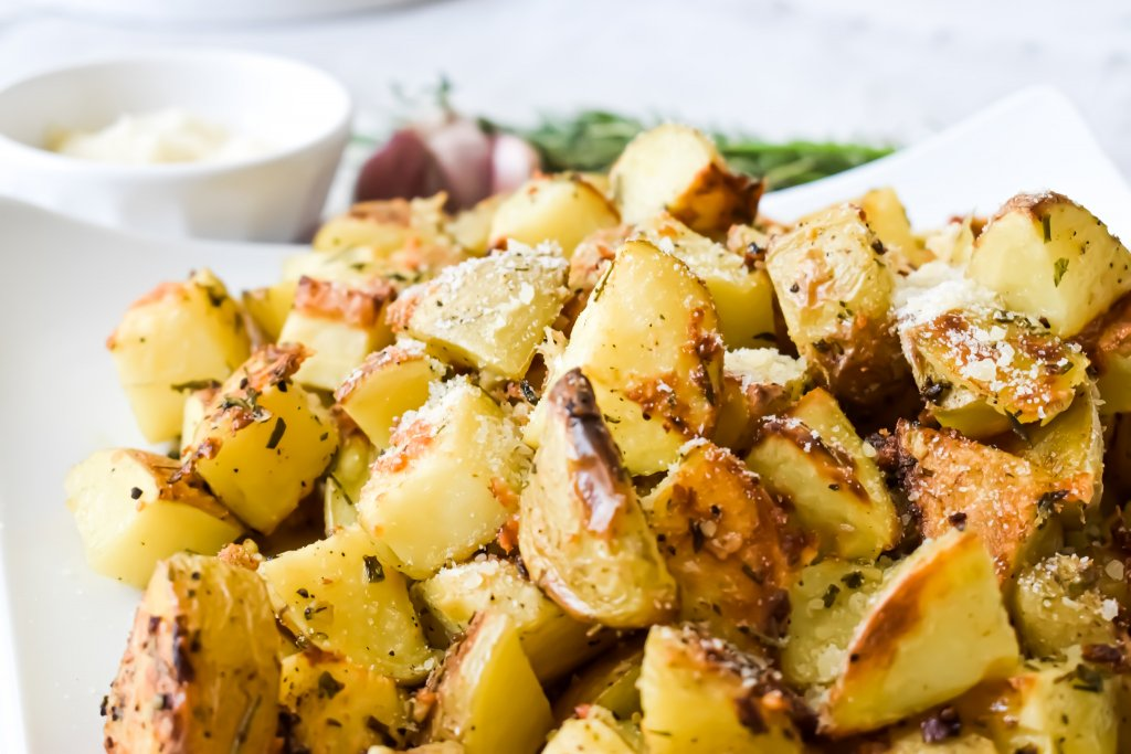 Herb Garlic Parmesan Roasted Potatoes served on a white plate photographed with rosemary, garlic and parmesan cheese
