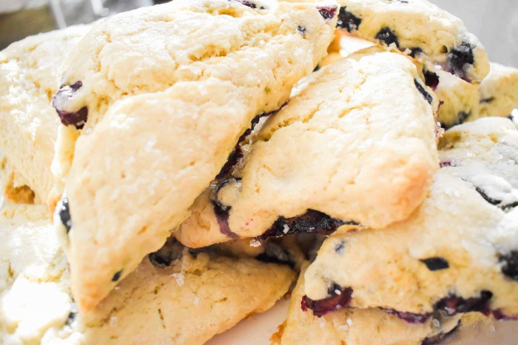 Blueberry scones piled on top of each other on a plate